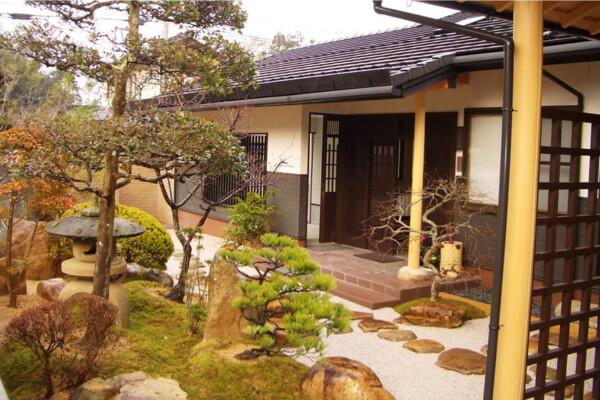 <b>玄関ポーチと中庭</b><br /> 新和風の玄関ポーチです。ポーチの奥に見える格子戸は車庫からの出入り口です。